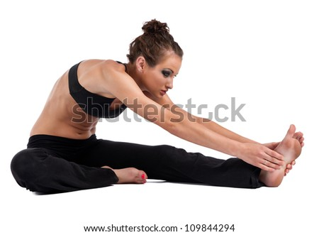 A beautiful young woman in a sports bra and yoga pants performing head to knee Yoga pose isolated on a white background. - stock photo