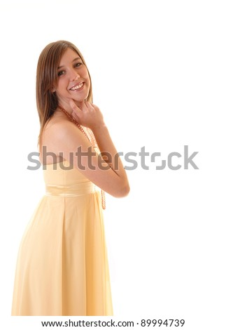 A beautiful young woman in a yellow dress standing in profile in the studio,  smiling into the camera and holding her head, on white background. - stock photo