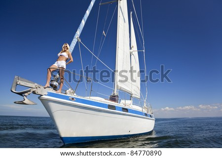 A beautiful young woman in shorts and a bikini standing on the front of a sail boat on a calm blue sea