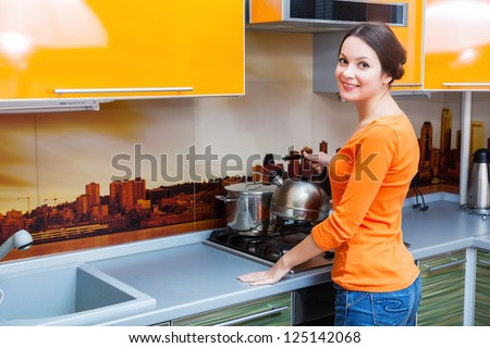 a beautiful young woman is putting a kettle - stock photo