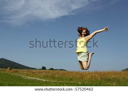 A beautiful young woman jumping in a field with a blue sky. - stock photo