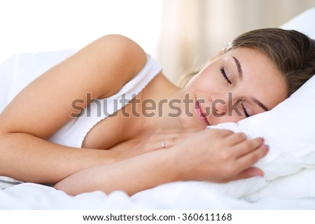 A beautiful young woman lying in bed comfortably and blissfully - stock photo