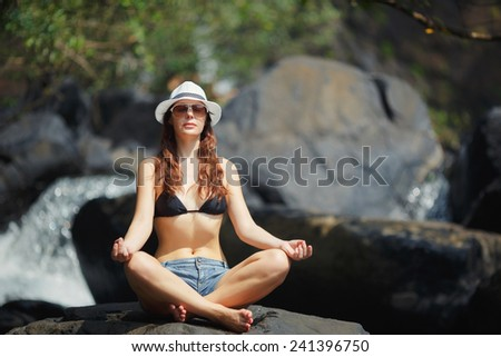 A beautiful young woman of European appearance, dressed in denim shorts, black leotard, white hat and glasses, employment practices yoga on a stone near mountain river. Yoga-lifestyle - stock photo