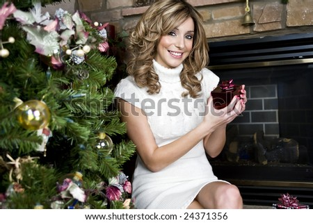 A beautiful young woman opening christmas presents - stock photo