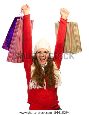 A beautiful young woman out shopping is thrilled to find the perfect gift - stock photo