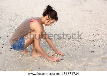 A beautiful young woman playing on beach sand with pebbles. - stock photo