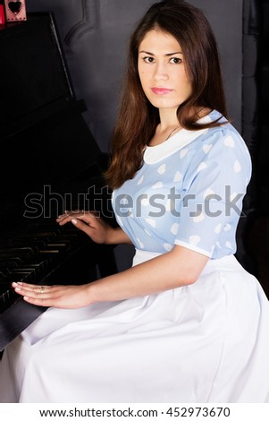 A beautiful young woman playing piano. - stock photo