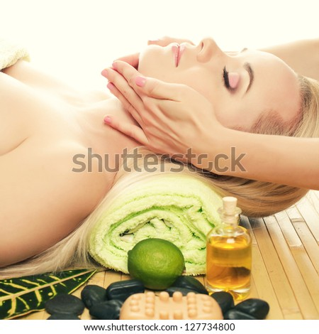 A beautiful young woman receiving facial massage at a spa salon. Perfect Skin. Skincare. Young Skin - stock photo