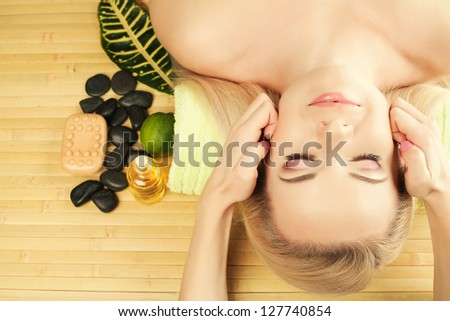 A beautiful young woman receiving facial massage at a spa salon. Perfect Skin. Skincare. Young Skin. Copy-space - stock photo