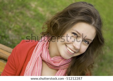 A beautiful young woman relaxing in the park on a bench. Laughs