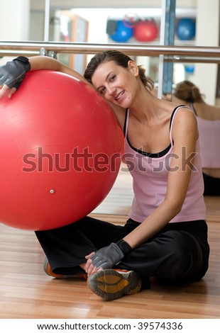 A beautiful young woman resting on her exercise ball after a Pilates Workout.