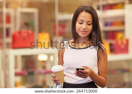 A beautiful young woman sending a text message in a mall - stock photo