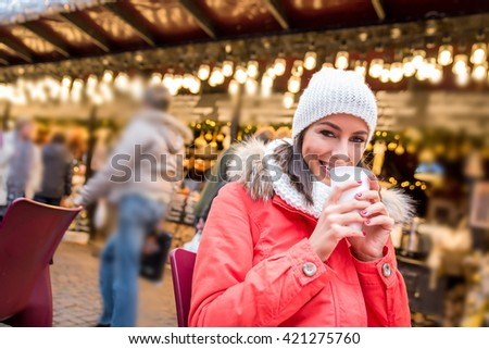 A beautiful young woman siting at a table and enjoying a cup of mulled wine on the christmas market.