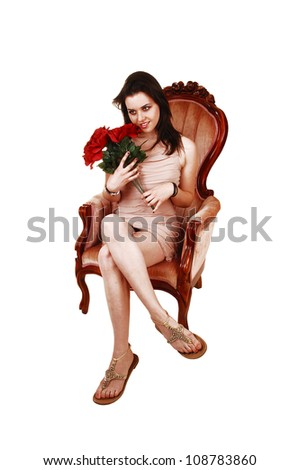 A beautiful young woman sitting in a pink armchair in a beige dress and holding a bunch of red roses, for white background.