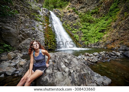 a beautiful young woman sitting in front of a waterfall - stock photo