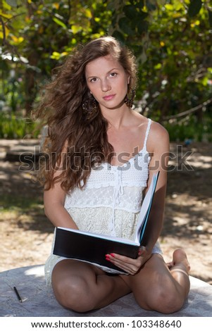 A beautiful young woman sitting in the shade with a pencil and notebook