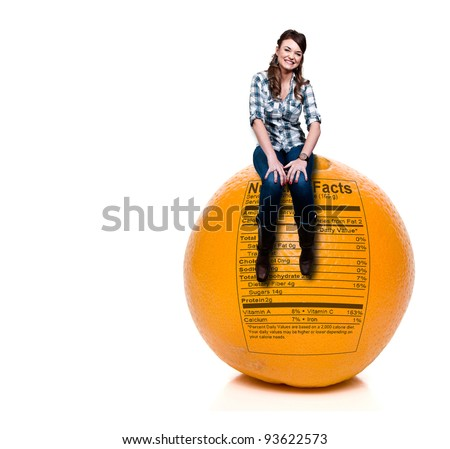 A beautiful young woman sitting on an orange with a nutrition label - stock photo