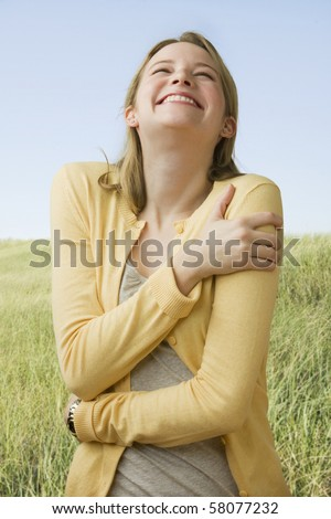 A beautiful young woman stands in a grass field while laughing.  Vertical shot.