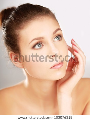 A beautiful young woman touching her face, isolated on white, closeup