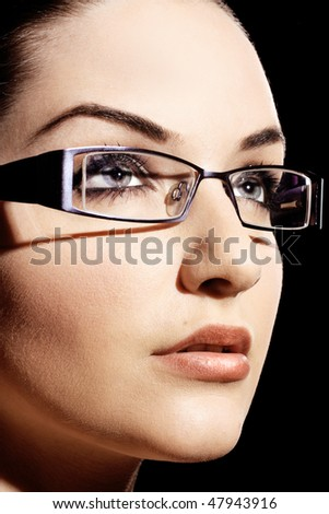 A beautiful young woman wearing fashionable glasses in front of a black background. - stock photo