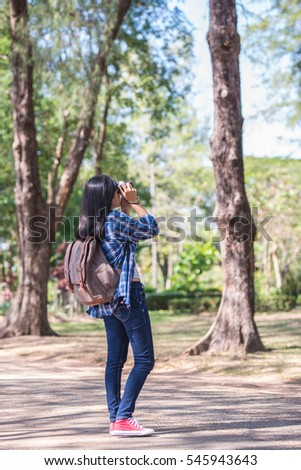 A beautiful young woman with backpack and a camera in pine plantations.
