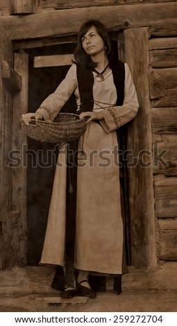 A beautiful young woman with dark hair in a black velvet historical dress is standing at the door of a forest log cottage, holding a basket, vintage sepia version