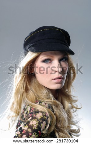 a beautiful young woman with hat in studio