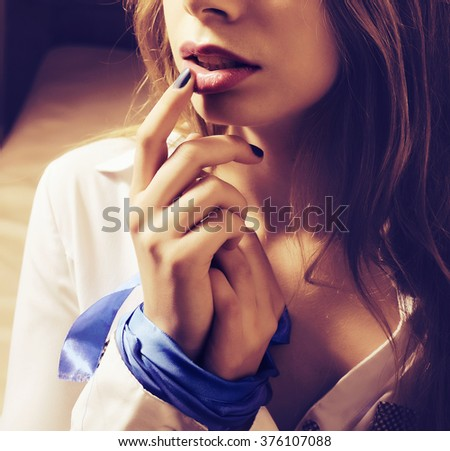A beautiful young woman with her hands tied - stock photo