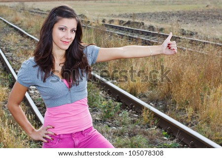 A beautiful young woman with long brown hair, wearing pink trousers and grey top, hitch-hiking on the railroad, smiling into camera - stock photo