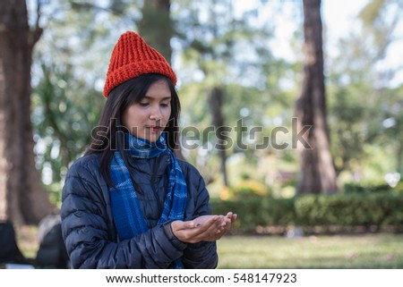A beautiful young woman with rad hat wearing a jacket in the park in winter.