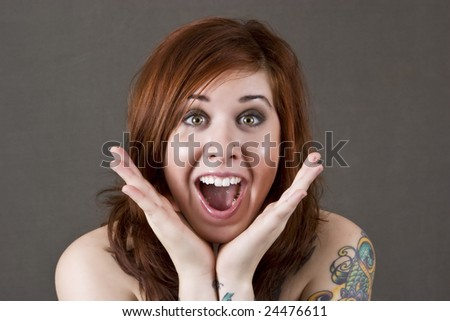 A beautiful young woman with tatoos looks surprised