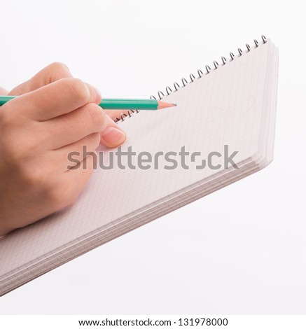 A beautiful young woman writes on the document table - stock photo