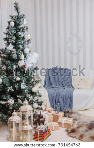 a beautifully decorated tree stands near a white sofa with a blanket under the christmas tree