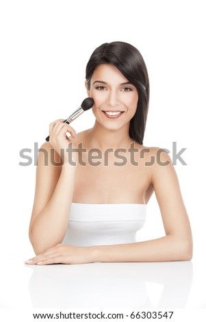 a beauty portrait of a young woman, shot on white background, holding a blush brush in one hand, up to her cheek, smiling. - stock photo