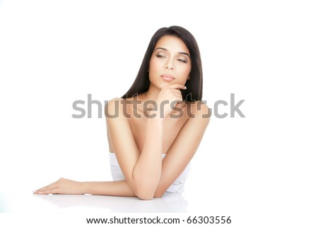 a beauty portrait of a young woman, shot on white background. she has both her elbows on a white table, with one hand to her chin, looking to the side. - stock photo