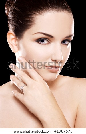 A beauty shot of a pretty young woman wearing a diamond ring in front of a dark background.