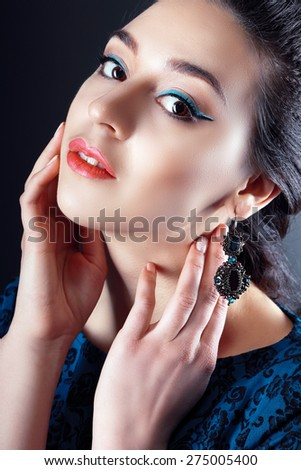 A beauty shot of a pretty young woman wearing butterfly earrings in front of a dark background. - stock photo