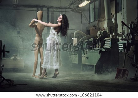 A beauty woman dances with a wooden dummy - stock photo