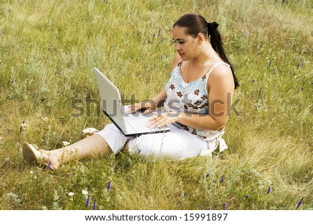 a beauty woman with notebook on the grass