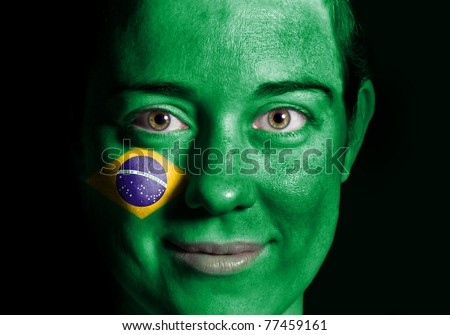 A beauty woman with the Flag of Brazil painted on her face