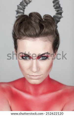 a beautyshot with a female with a wicked hairstyle Creative face paint portrait .Day of the Dead persons.halloween - stock photo