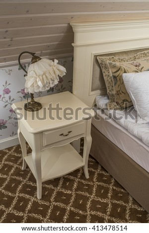 a bedside table with a lamp in the bedroom - stock photo