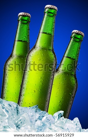 A beer bottle sitting in a container of ice on blue background