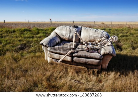 A beer stained party couch haunted by parties past, discarded in a ditch on a rural prairie road.
