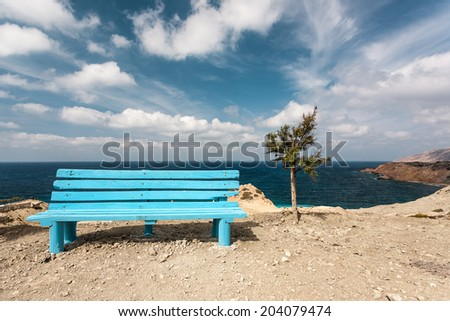 A bench, laying on the edge of a cliff near the sea, on a rocky coastline, during daylight, on a summer, with a cloudy blue sky, located in the Aegean sea, in the island of Karpathos, Greece. - stock photo