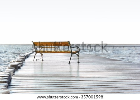 A bench on an icy footbridge at the lake Neusiedl, Burgenland.