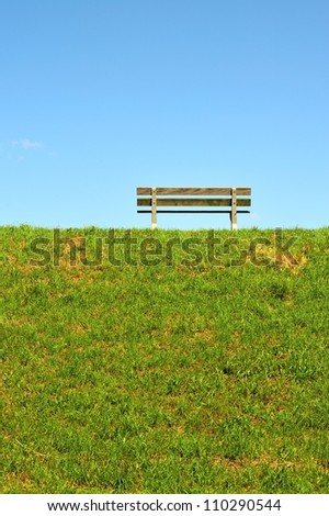 A bench on top of the dike - stock photo