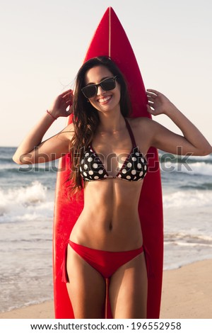 A beuatiful and sexy surfer girl at the beach with her surfboard - stock photo