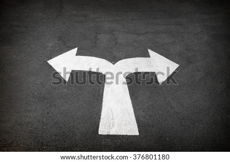A bi-directional arrow symbol on a wet asphalt road for the conc - stock photo