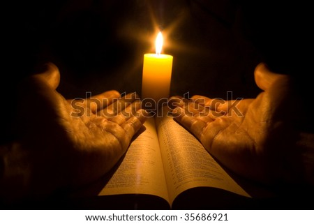 A bible open on a table next to a candle